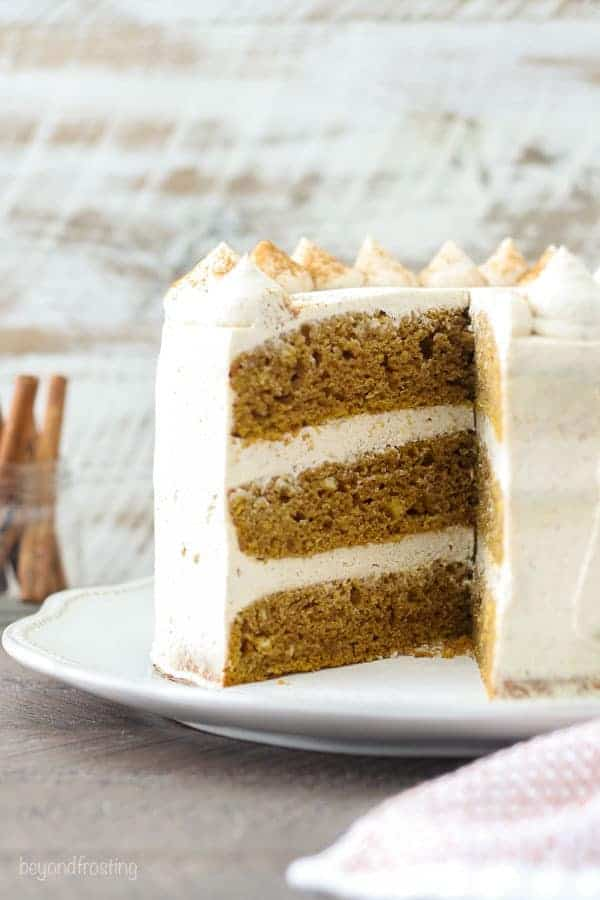 A side view of an 8-inch 3 layer pumpkin cake frosting with mascarpone whipped cream.