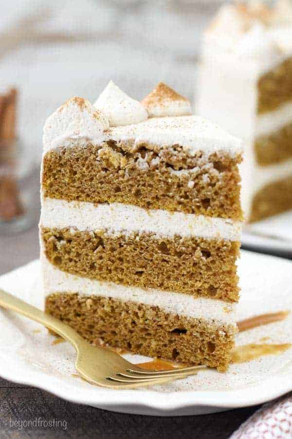 A tall slice of pumpkin cake on a white plate with caramel drizzle and a gold fork