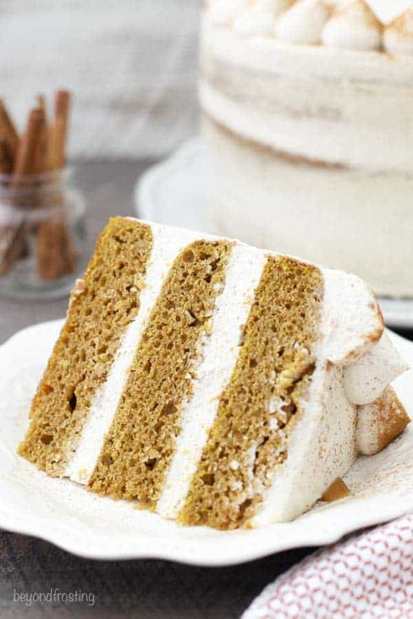 A close up of a 3-layer pumpkin cake with plenty of whipped cream frosting layered in between