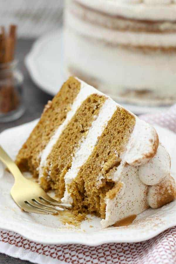 A slice of pumpkin cake on a decorated white cake with several bites taken out of it