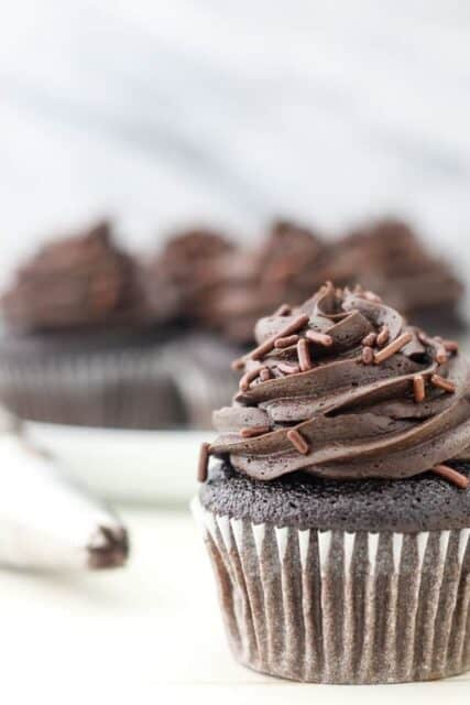 A close up photo of a chocolate cupcake frosted with chocolate frosting with chocolate sprinkles and and a piping bag in the background