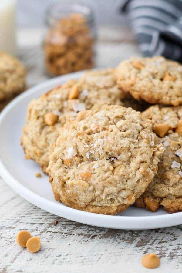 A gorgeous plate of butterscotch oatmeal cookies loaded with butterscotch chips and sprinkled with a flakey sea salt
