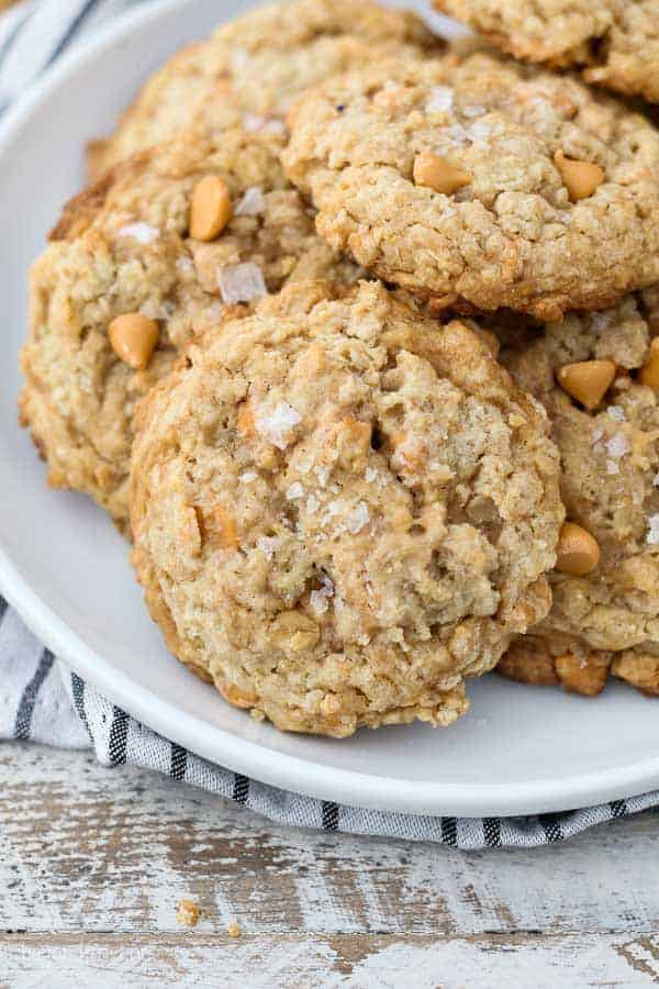 A white rimmed plate with stacks of butterscotch oatmeal cookies sprinkled with flakey sea salt