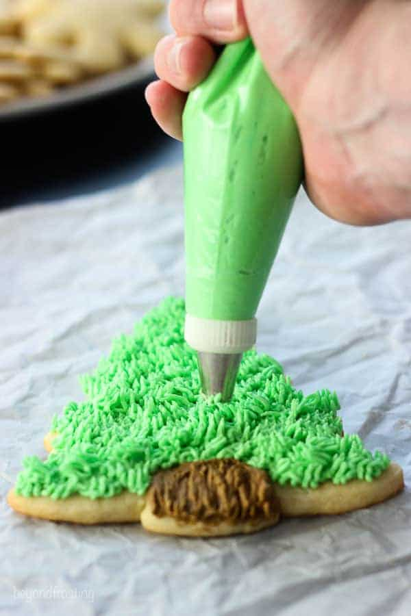 A piping tip with green frosting on a Christmas tree cut out sugar cookie