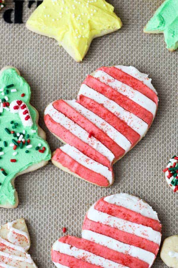 A cut out sugar cookie with red and white striped frosting and red sprinkles.