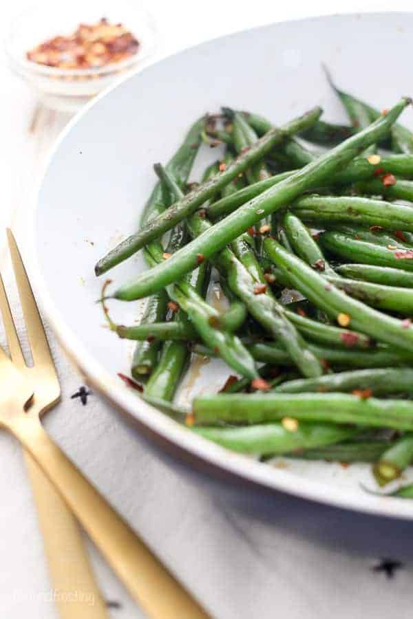 A close up side view of fresh sauteed green beans in a blue skillet garnished with crushed red pepper