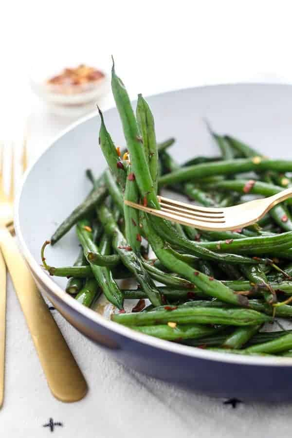 A gold fork holding up a big helping of fresh sautéed green beans