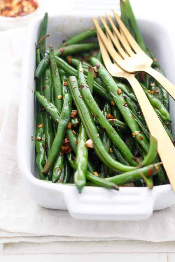 A small casserole dish filled with green beans and 2 gold forks.