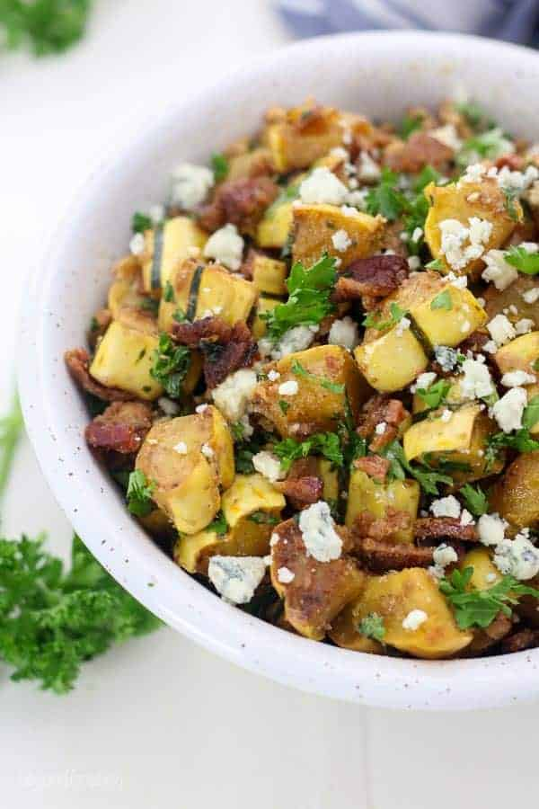 An overhead view of a cold squash salad loaded with crumbled bleu cheese and parsley