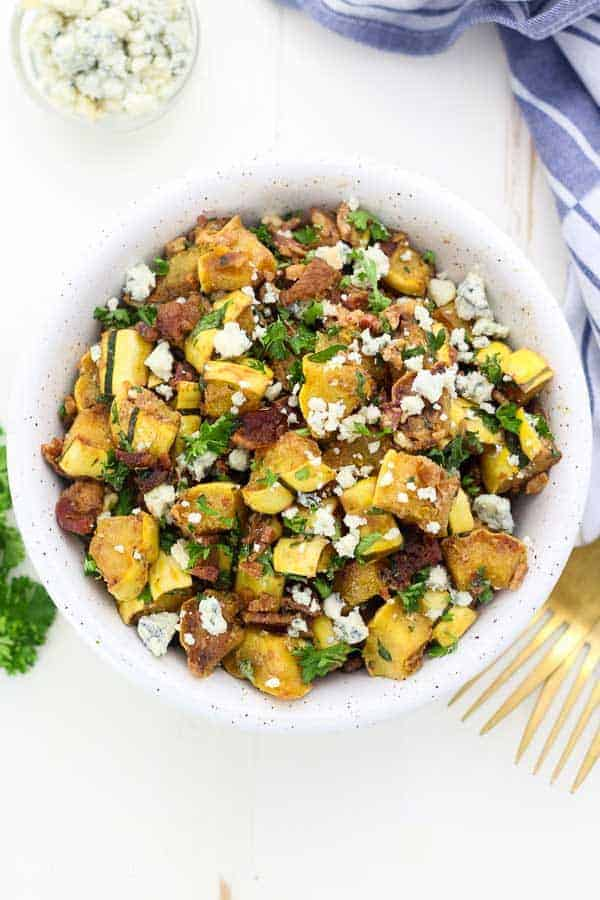An overhead view of a colorful, delicious looking winter squash salad with lots of green parsley.