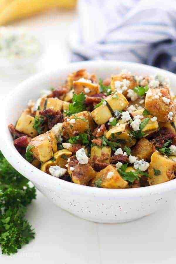 A gorgeous winter squash salad in white bowl. It's chopped delicata, lots of fresh parsley, bacon and bleu cheese crumbled.