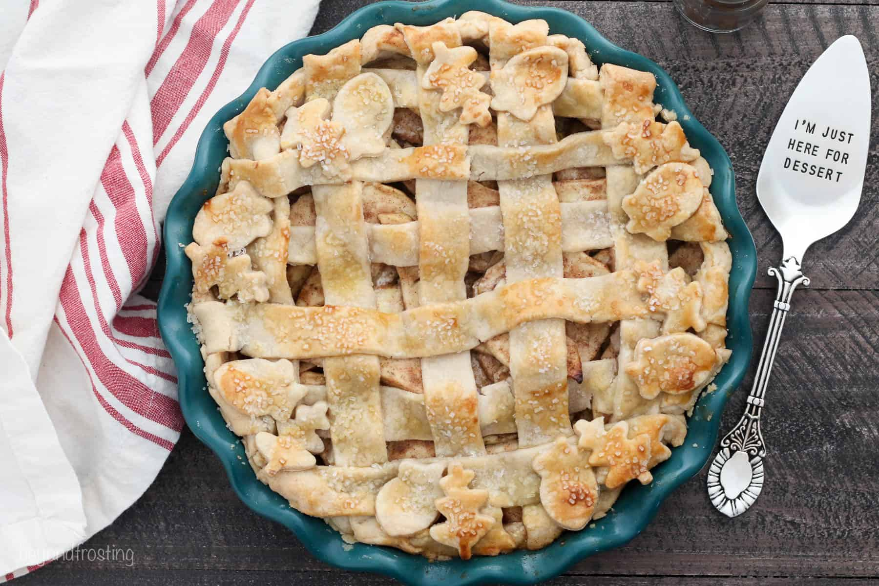 An overhead shot of a lattice topped apple pie in a dark teal pie plate