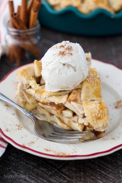 An overhead shot of a big slice of apple pie on a red rimmed plate and a silver fork with a scoop of ice cream on top.