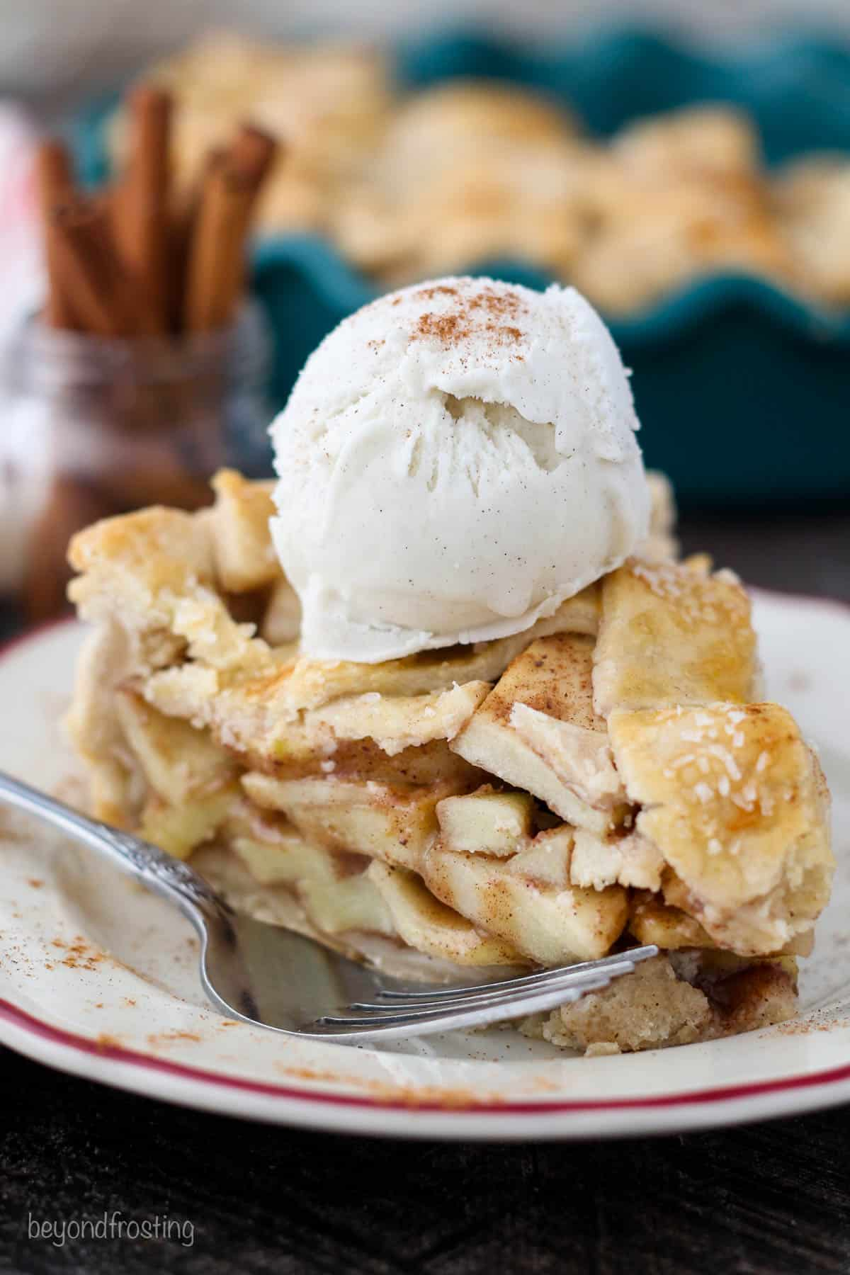 A close up a big slice of apple pie with ice cream and cinnamon on top