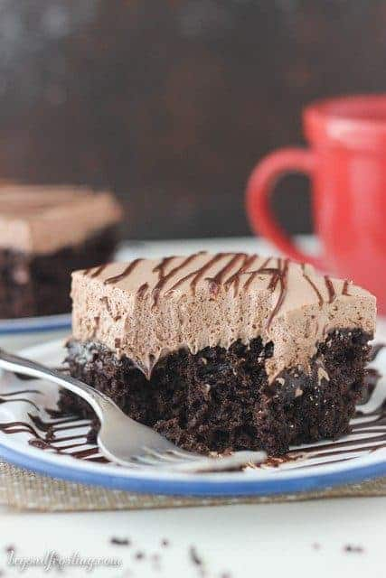 A slice of Hot Chocolate Poke Cake with a bite missing and a fork resting next to it.