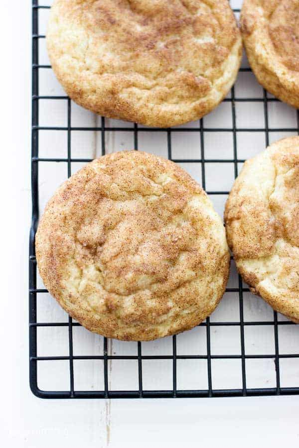 An overhead shot of snickerdoodle cookies on a black wire cooling rack