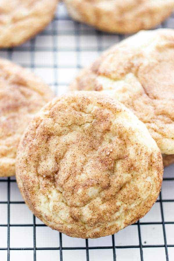 A close up of the most delicious looking snickerdoodle cookie recipe on a black wire cooling rack