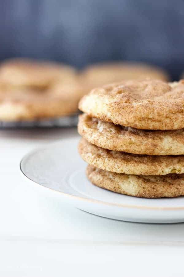 A small stack of 4 snickerdoodle cookies on a white plate