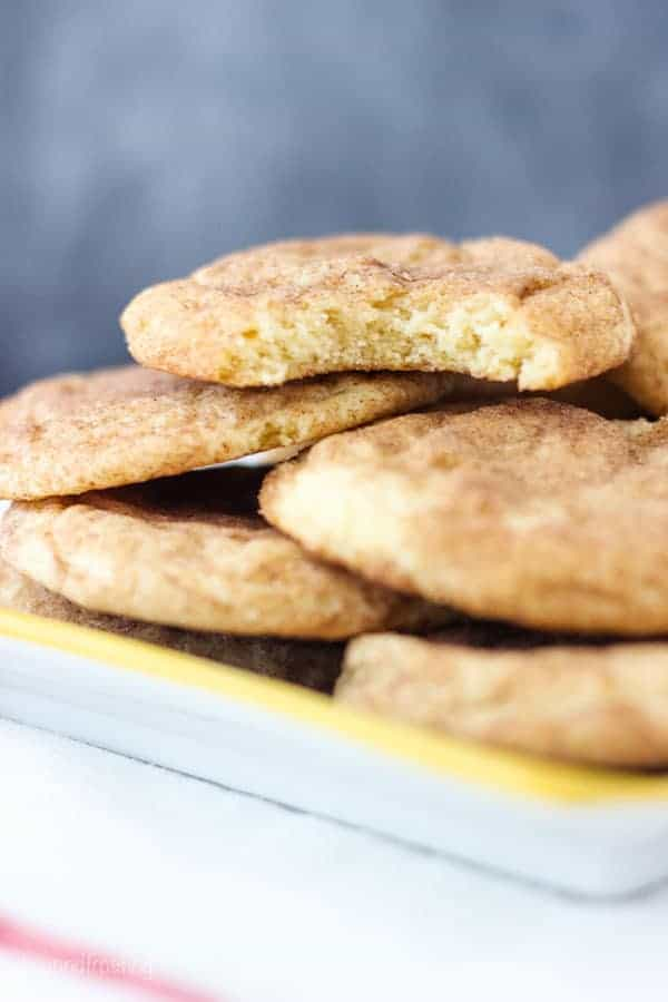 A stack of snickerdoodle cookies on a yellow rimmed plate