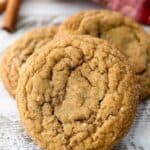 A close up shot of a molasses cookie leaving up against a stack of more cookies
