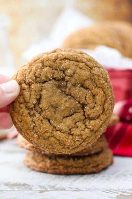 Two fingers holding up a big molasses cookie rolled in sugar