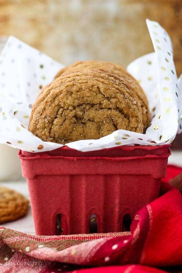 A cute red berry container with white tissues paper and some molasses cookies hanging out of the top
