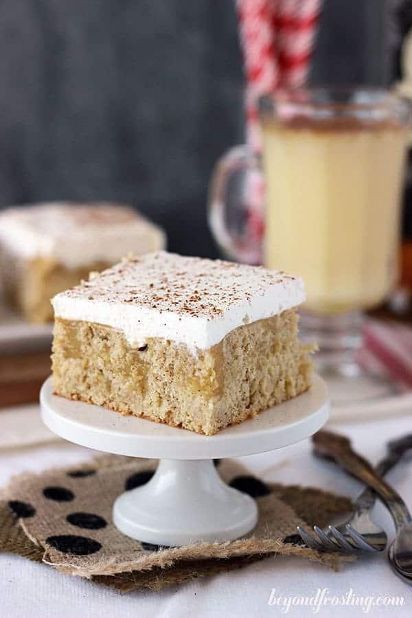 A slice of eggnog poke cake on a mini white cake stand sitting on polka dot printed burlap
