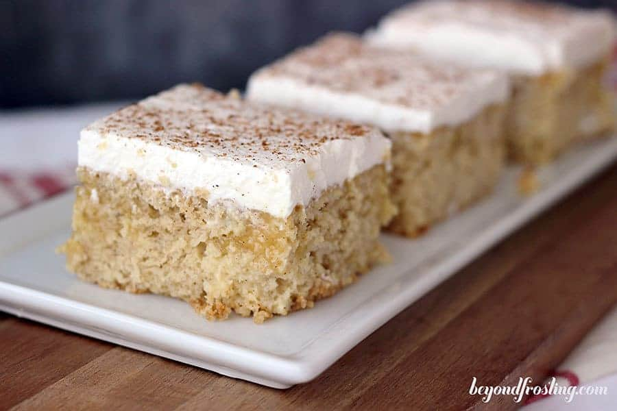A wide shot of 3 slices of eggnog poke cake on a white rectagnle plate