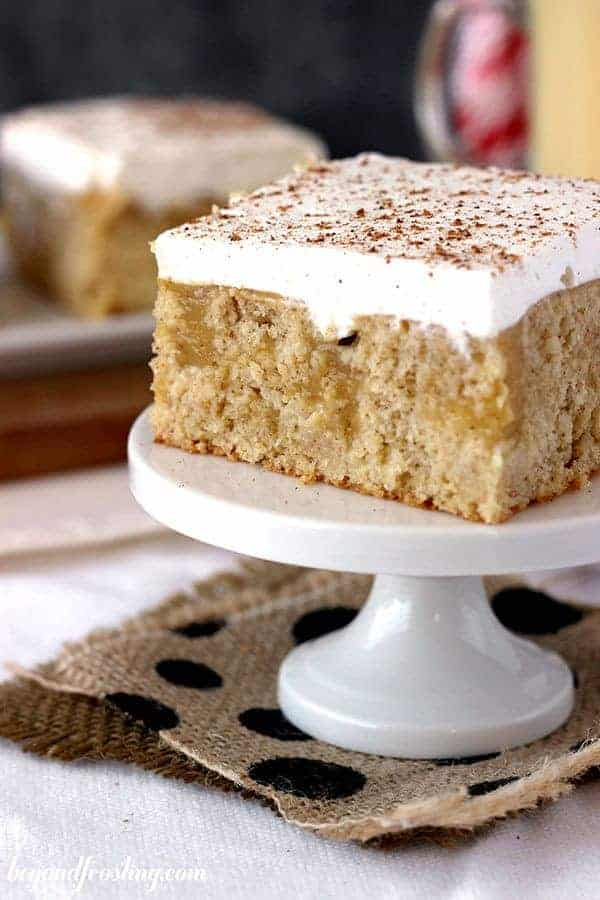 A close up of an eggnog poke cake, with pockets of pudding in the middle and whipped cream on top