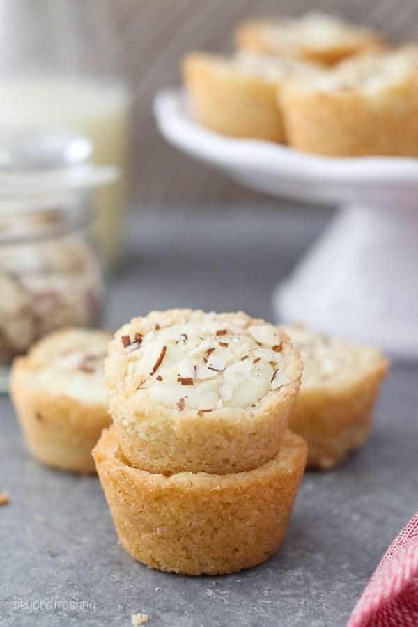 Two mini cookie cups stacked, the cookie on top has diced almonds on top.