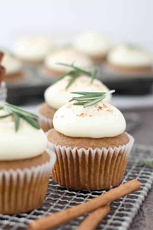 Three gorgeous gingerbread cupcakes with white cupcake wrappers and a rosemary garnish are sitting on a wire baking rack