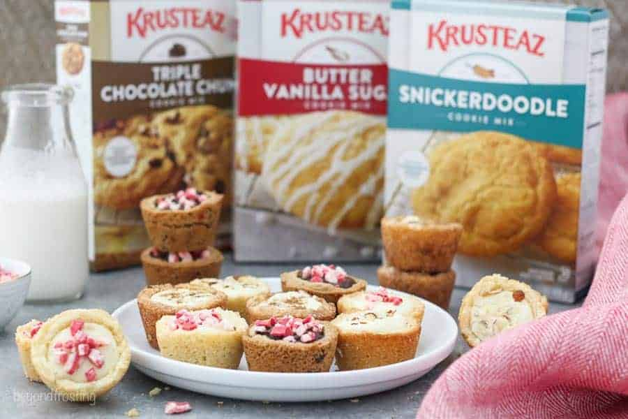 A white rimmed plate filled with various cookie cups and 3 boxes of Krusteaz cookie mix in the background.