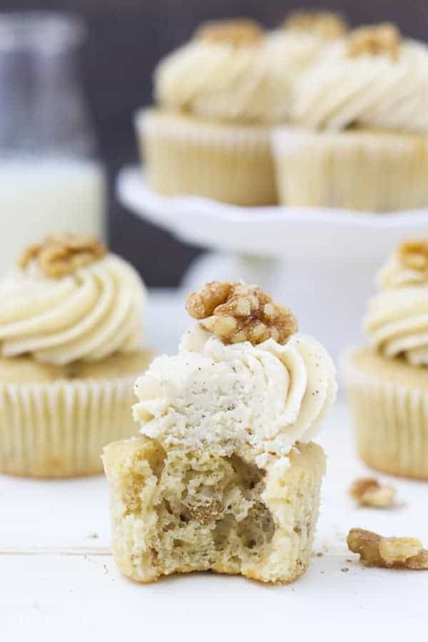 a big bite is taken out of this cupcake exposing the airy inside of the cupcake with walnuts.