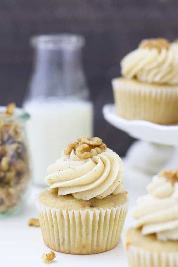 A cupcake is sitting in front of a small glass of milk, a jar of walnuts and a small white cake stand with cupcakes on top.