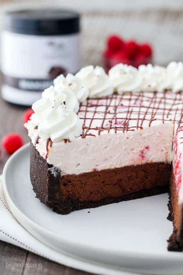 A whole raspberry chocolate mousse cake with a big slice but out of it. The top is drizzled with a chocolate glazed and whipped cream.