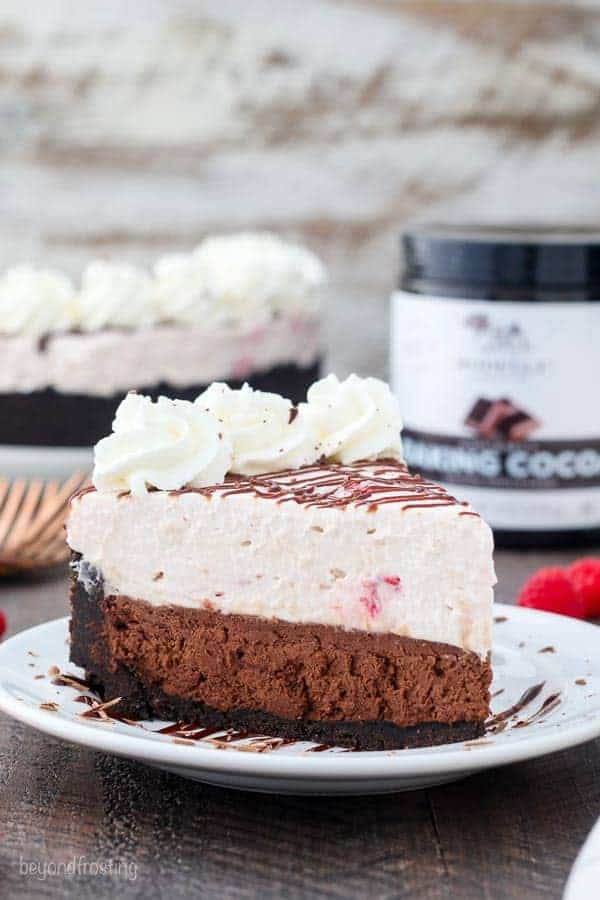 A gorgeous slice of mousse cake, it's two layers. The bottom layer is a chocolate mousse and the top layer is a raspberry mousse and it covered with drizzled chocolate and whipped cream. There's a jar of Rodelle cocoa powder blurred out in the background.