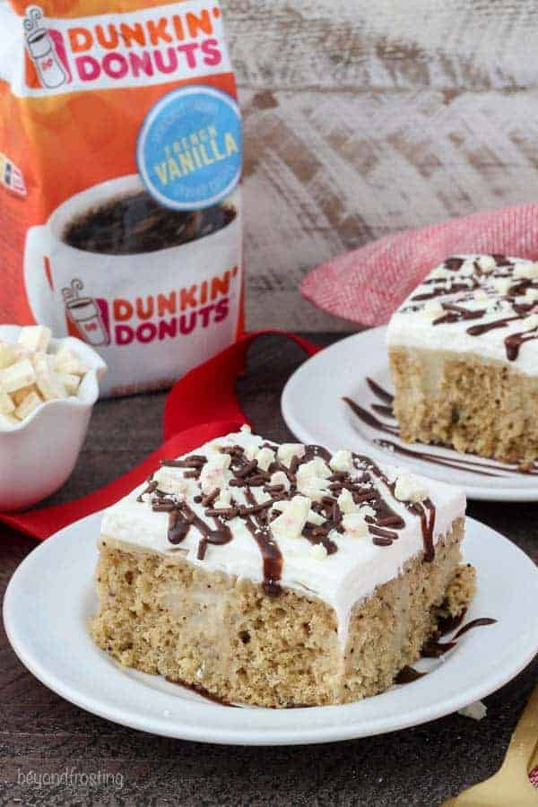 A white plate with a slice of cake covered in whipped cream, fudge and peppermint bark. There's a bag of Dunkin' Donuts French Vanilla coffee in the background.