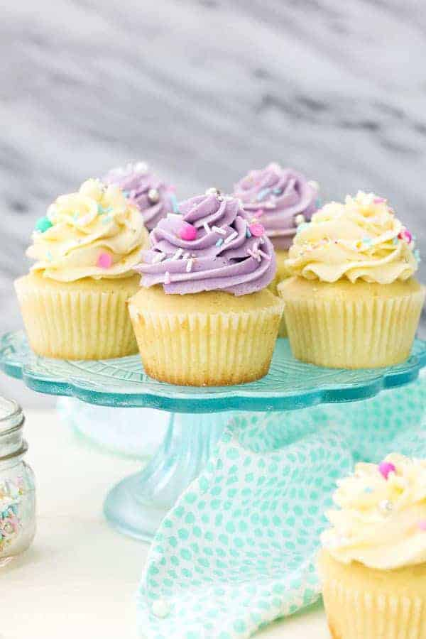 A clear blue glass cake stand with 5 cupcakes on top, 3 of them have purple frosting and two of them have white frosting. They have some very pretty colorful sprinkles on top