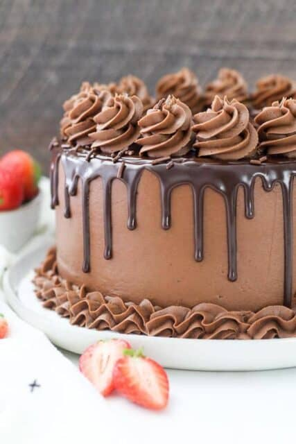 An side view of the top of a chocolate cake that is swirled with chocolate ganache, chocolate sprinkled and covered with chocolate frosting rosettes. Sliced strawberries surround the cake.