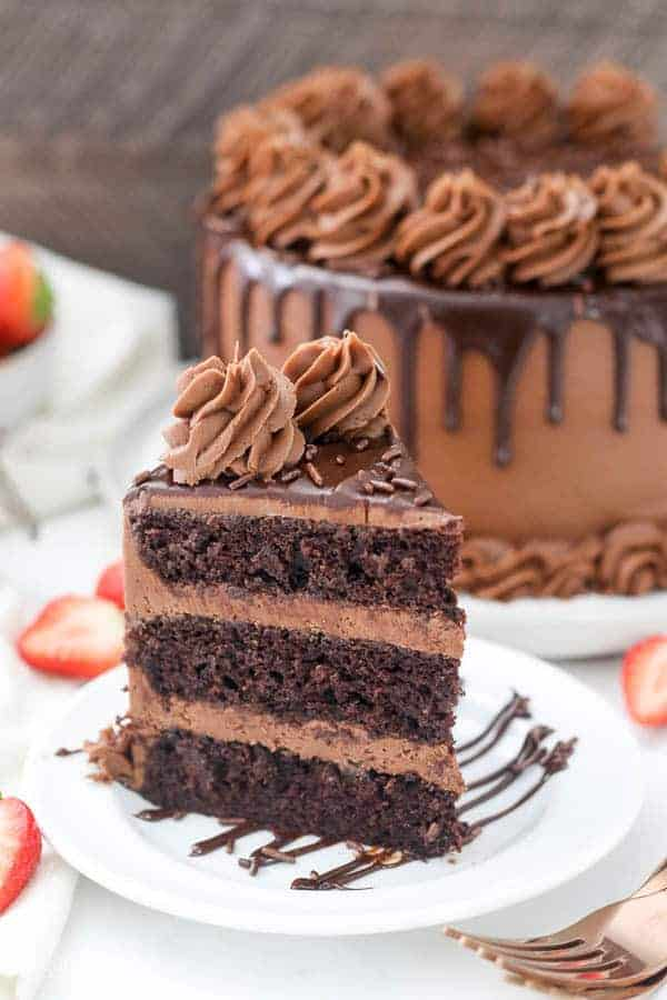 A Tall Slice Of Chocolate Cake On White Plate Drizzled With The