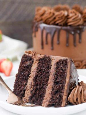 A mouthwatering photos of a big slice of chocolate cake with layered of chocolate frosting and finished with a chocolate ganache. The slice is laying sideways on a white rimmed plate.