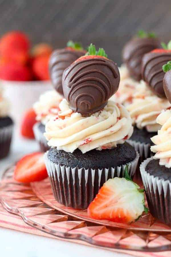 A gorgeous chocolate cupcake with a pretty pink strawberry frosting and a chocolate covered strawberry on top. It's sitting on a pink glass cake plate with a pink striped towel underneath and fresh strawberries scattered around.