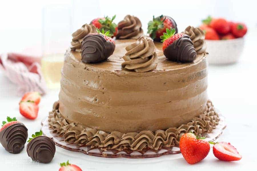 A wide shot of a chocolate layer cake with chocolate frosting, it's garnished with chocolate covered strawberries