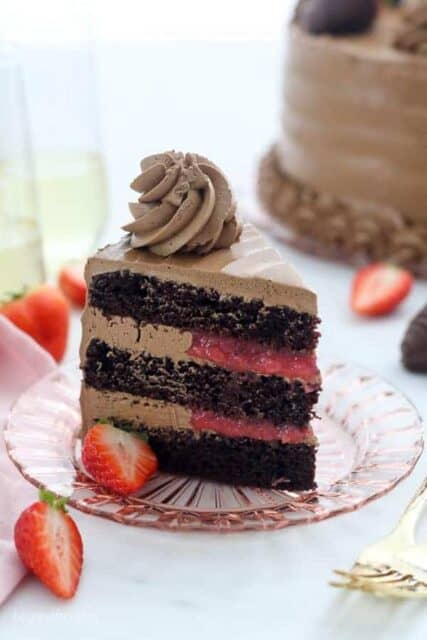 A slice of dark chocolate cake with a strawberry filling and a silky buttercream frosting stands tall on a pink tinted glass plate garnished with strawberries.