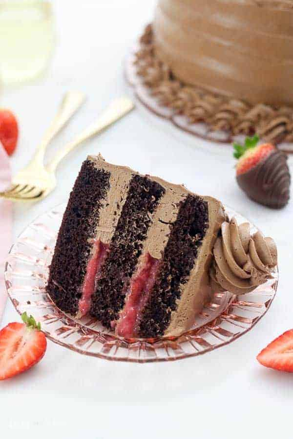 An overhead view of a slice of dark chocolate cake with a strawberry filling and a silky buttercream frosting, there are a few strawberries scattered around and two gold forks blurred out in the background.