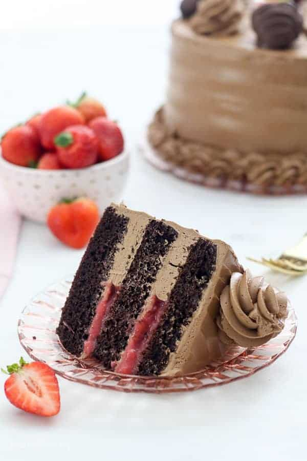 A slice of dark chocolate cake with a strawberry filling and a silky buttercream frosting sitting on a light pink plate, it's surrounded by strawberries