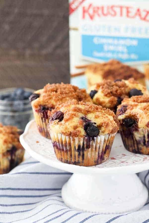 A blueberry coffee cake muffin on a white cake plate with a box of Krustez Gluten Free mix inin the background.
