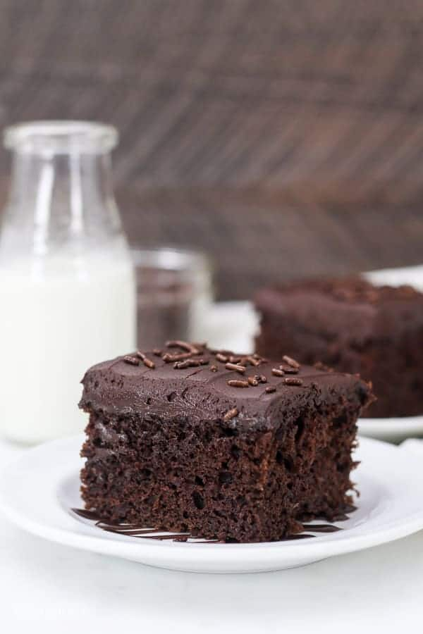 A chocolate buttermilk cake with a layer of chocolate buttermilk frosting on top and garnished with sprinkles. There's a slice of cake blurred out in the background and a tall glass of milk as well.