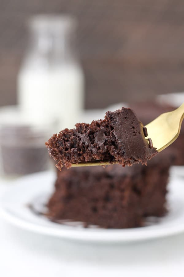 A gold fork with a big bite of chocolate cake on the end of the fork.