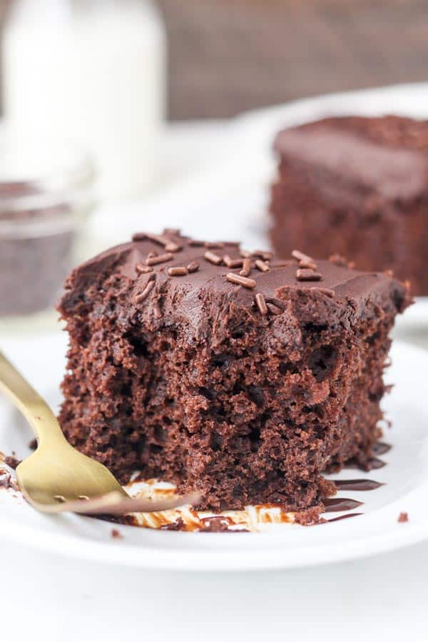 A gooey slice of chocolate cake with a few bites taken out of it showing all the air bubbled inside.